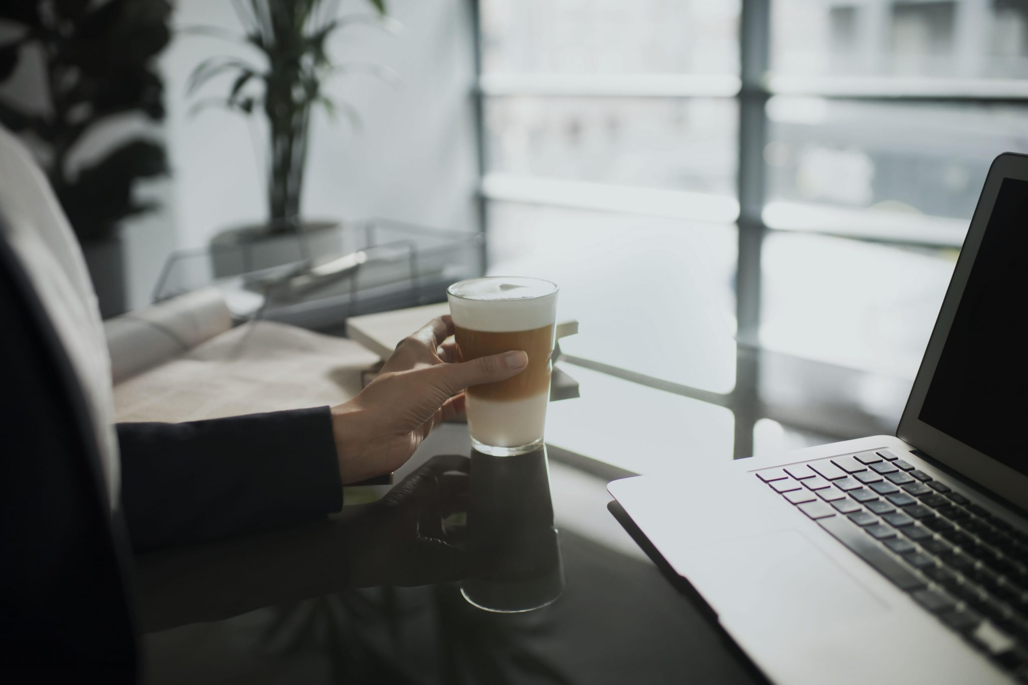 Tomar café delante de un ordenador