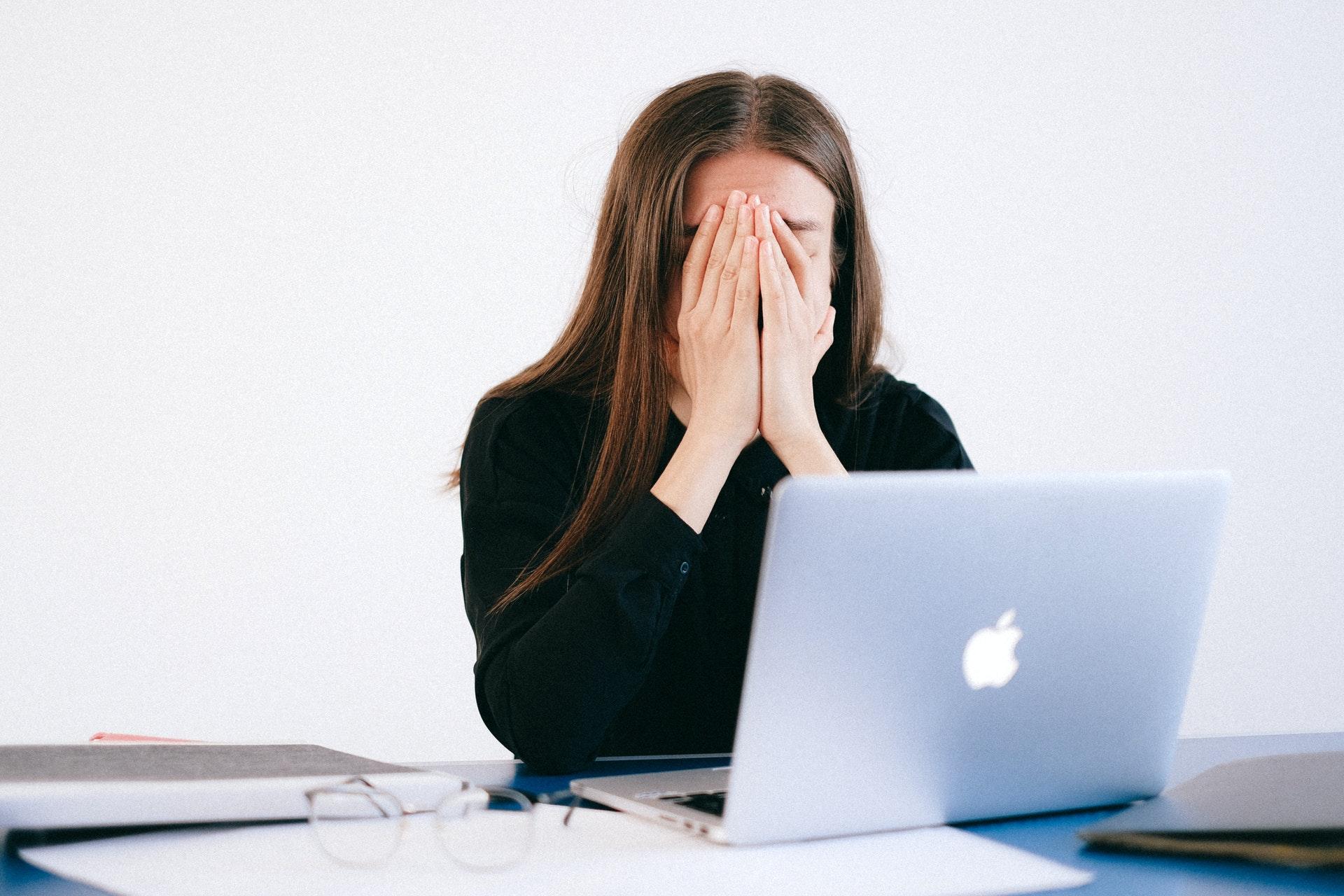 chica tapándose la cara delante de un ordenador portátil