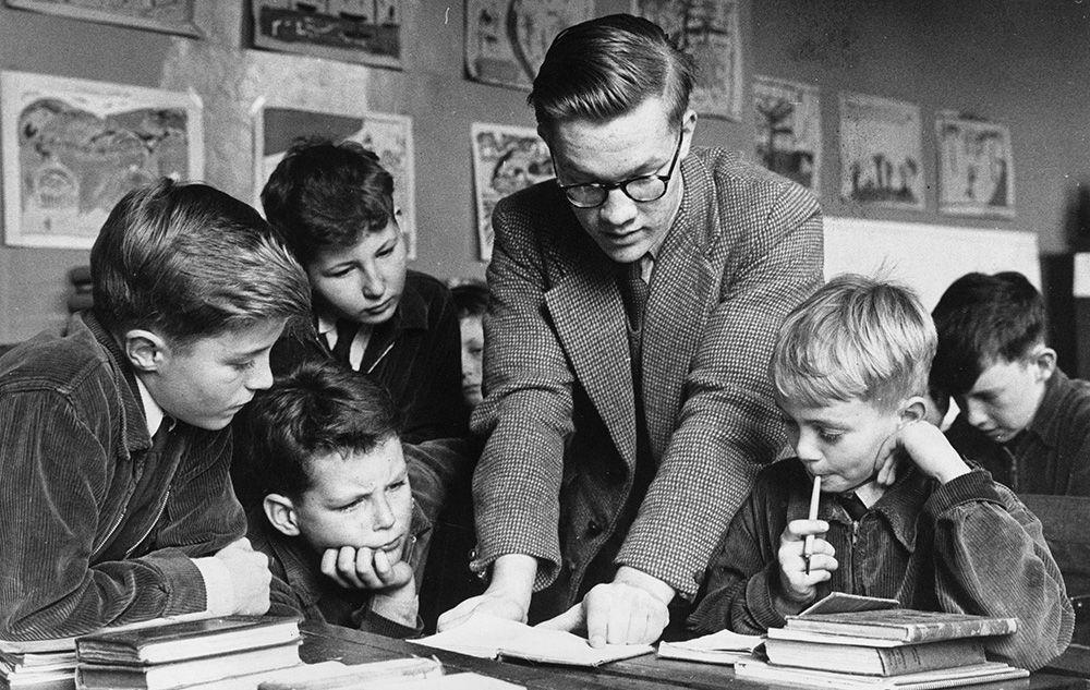 Un profesor señala un libro mientras los alumnos le escuchan. Estudiar. Escuela. Alumno. Profesor