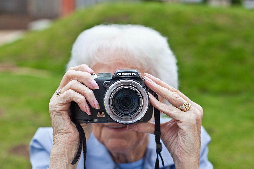 Una señora mayor hace una foto con una cámara Olympus