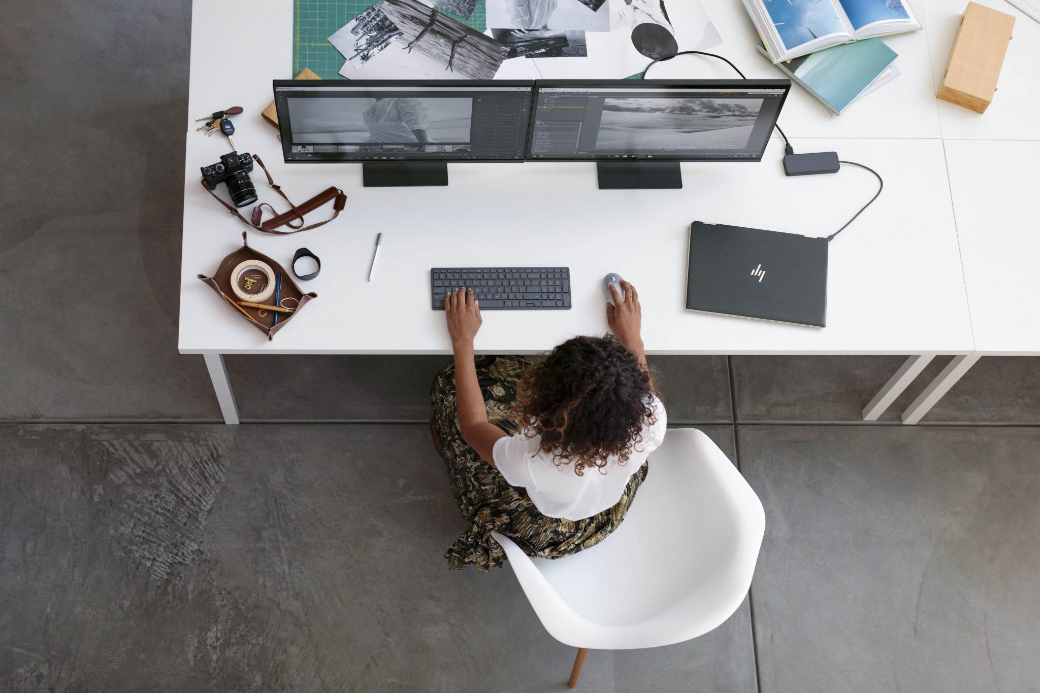 HP - Una chica delante de dos pantallas de ordenador con un portátil a su izquierda