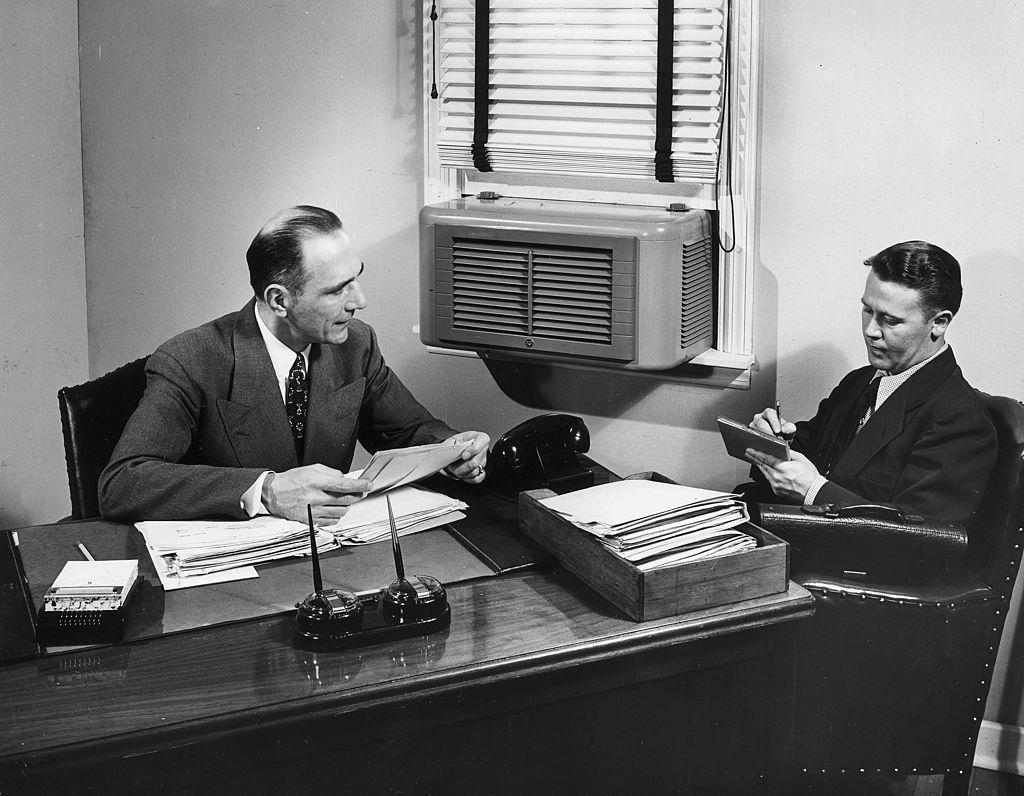 Un hombre de negocios toma notas mientras su jefe se sienta detrás de un escritorio y lee las cartas. Un aire acondicionado está montado en la ventana. Foto: Lambert/Getty Images