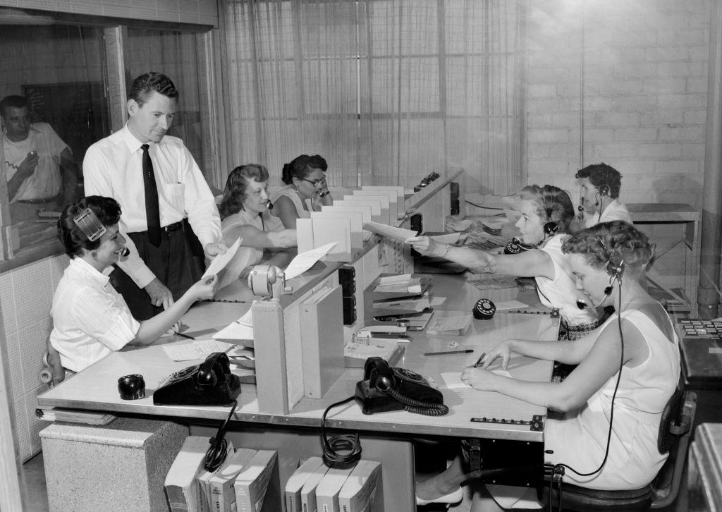 Un grupo de mujeres con auriculares están sentadas en un call center, mientras que un hombre que está de pie revisa unos documentos con una de ellas. Foto: Kirn Vintage Stock/Getty Images