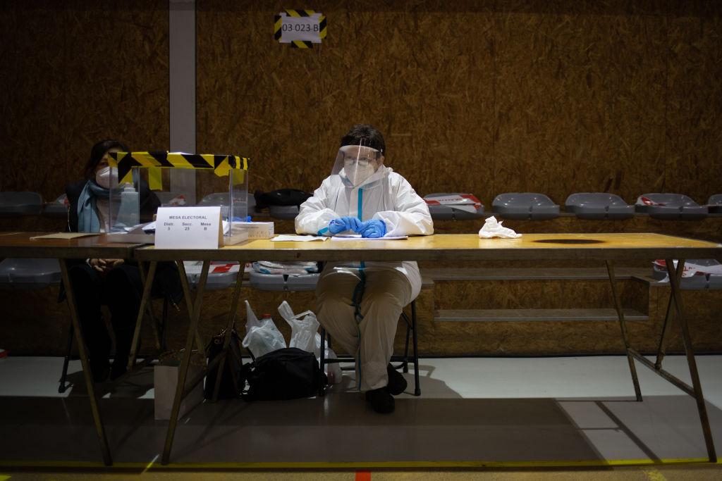 Una mujer con traje EPI en una mesa electoral en Barcelona. Getty.