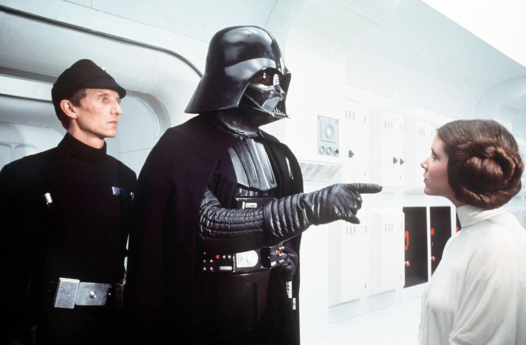 El actor británico David Prowse y la actriz estadounidense Carrie Fisher en el set de 'Star Wars: Episodio IV - Una nueva esperanza' escrita, dirigida y producida por Georges Lucas. Foto: Sunset Boulevard/Corbis (Getty Images)