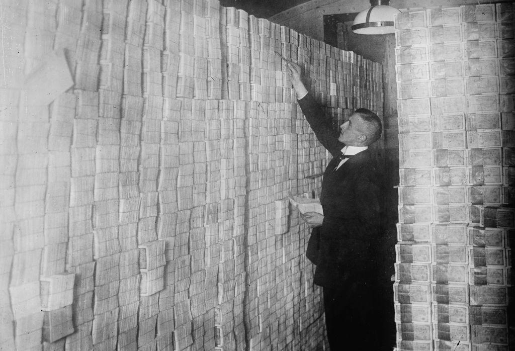 La inflación en la Alemania de Weimar hace que el papel moneda se apile desde el suelo hasta el techo en un banco de Berlín (Alemania). Un banquero lo está contando. Foto: Buyenlarge (Getty Images)