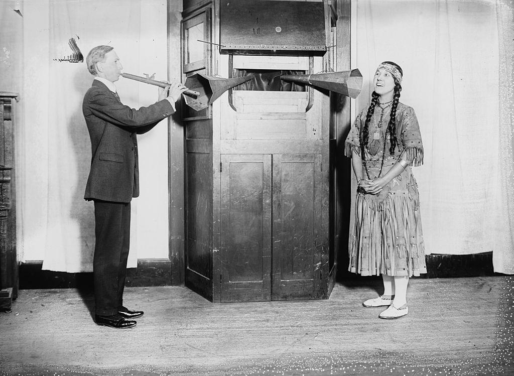 Un cantante y un flautista introducen sus sonidos a través de megáfonos en una caja de grabación; la mujer está vestida como una princesa india Foto: Buyenlarge (Getty Images)