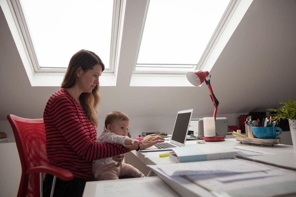 Una mujer trabaja mientras cuida de su hijo durante el confinamiento. Getty.